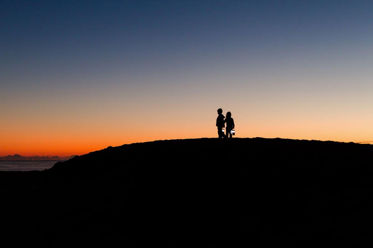 kids climbing sand dunes at sunset at Jessie Honeyman State Park in Oregon