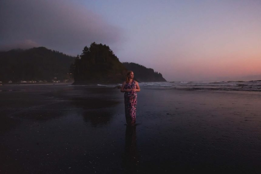 pregnant woman standing watching the sunset at the Oregon Coast