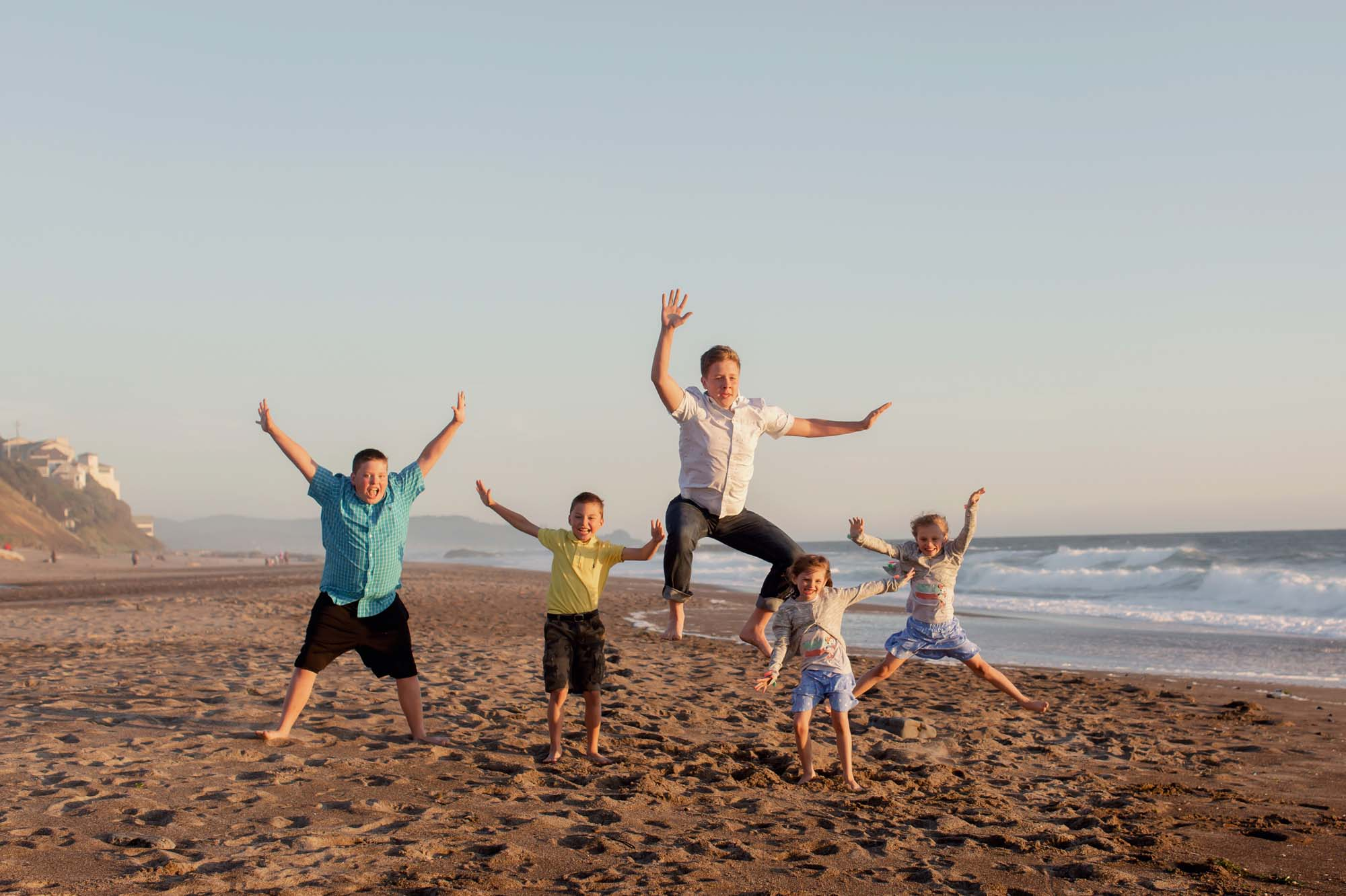 kids jumping at the beach in the oregon coast