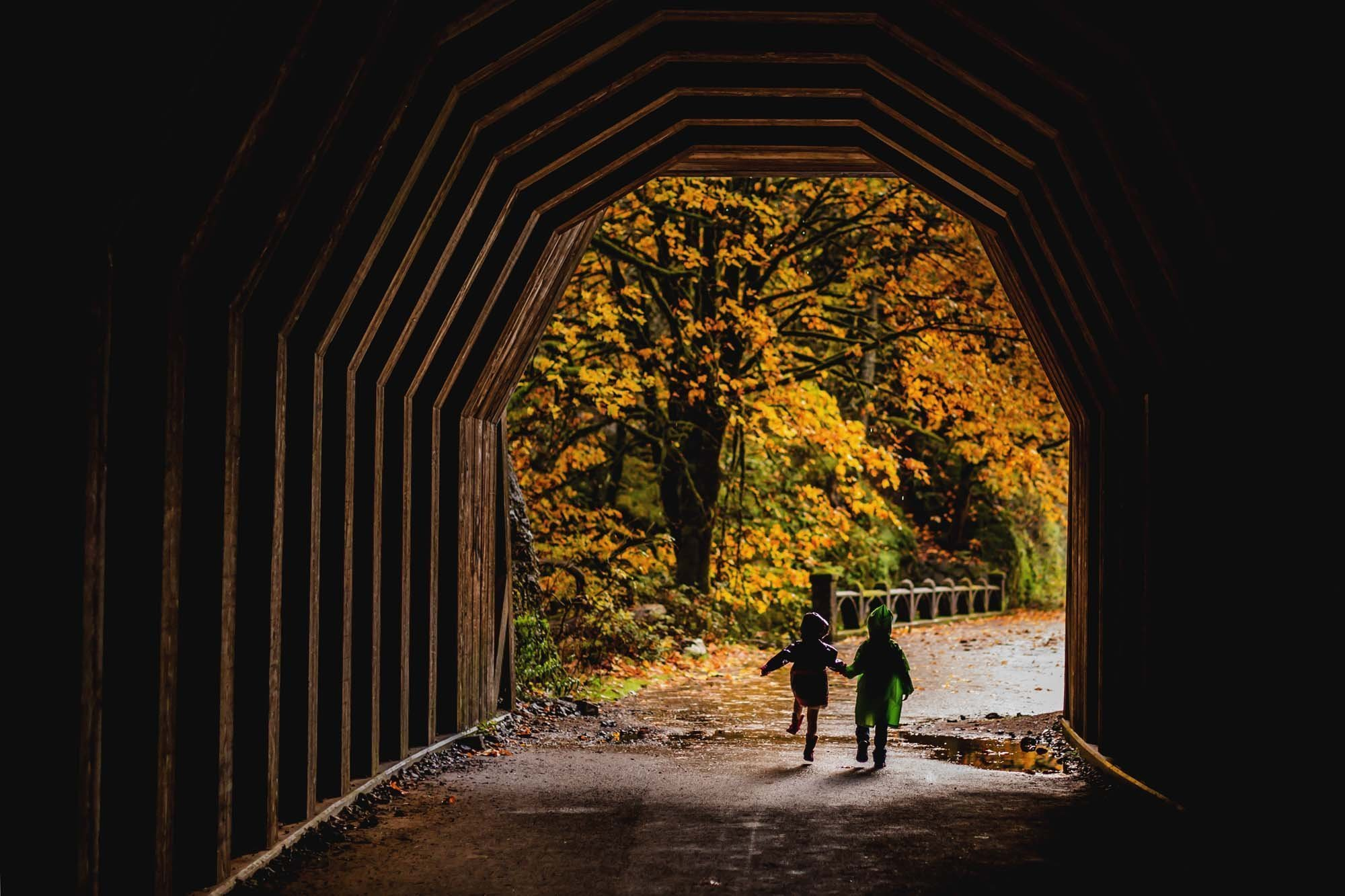 PNW kids running in Oneonta Falls Tunnel in the fall