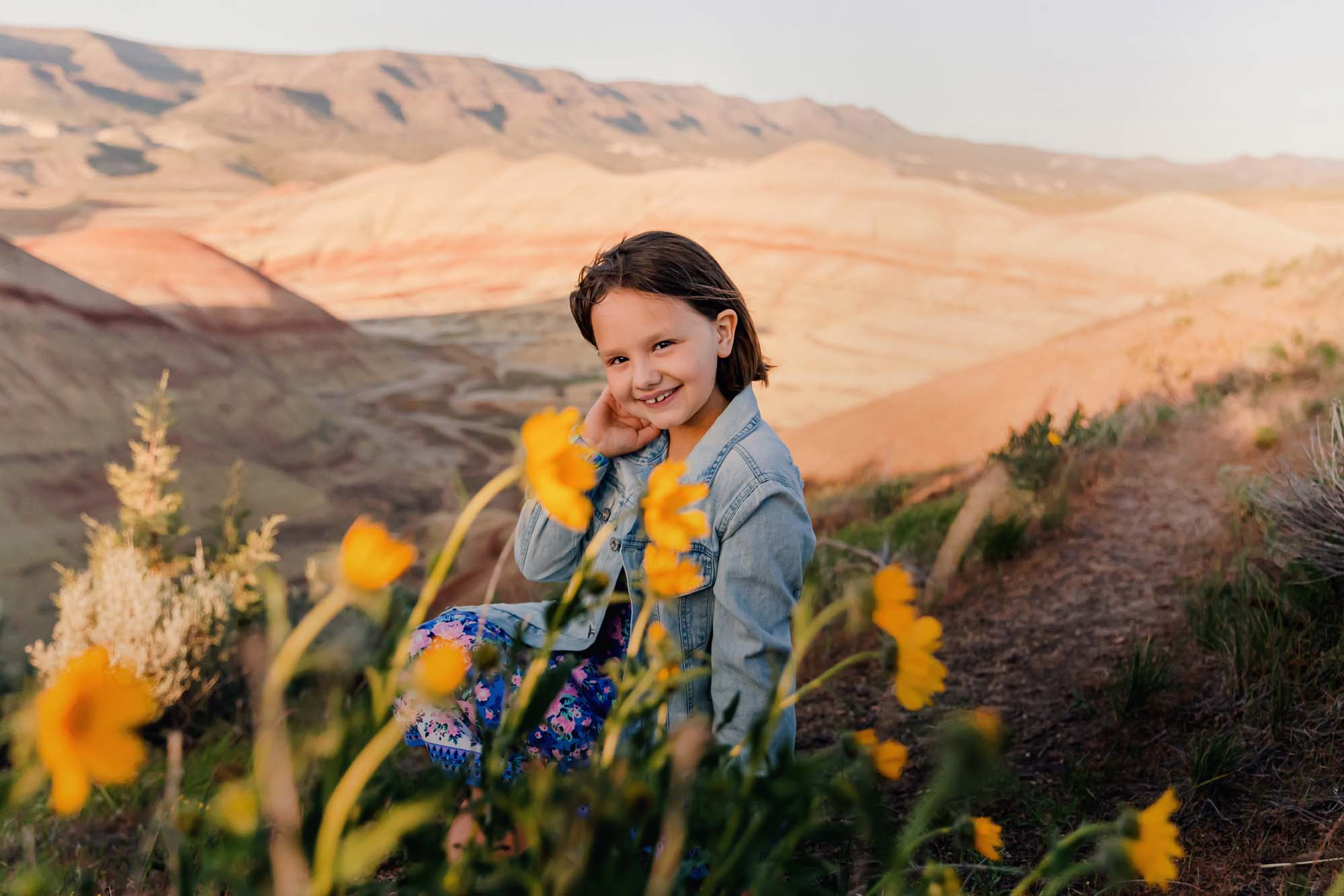 girl sitting near wildflowers in the painted hills overlook oregon